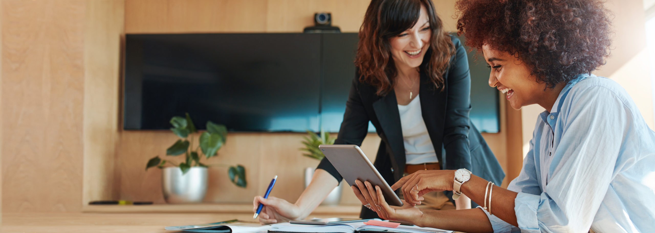 women laughing at tablet in office