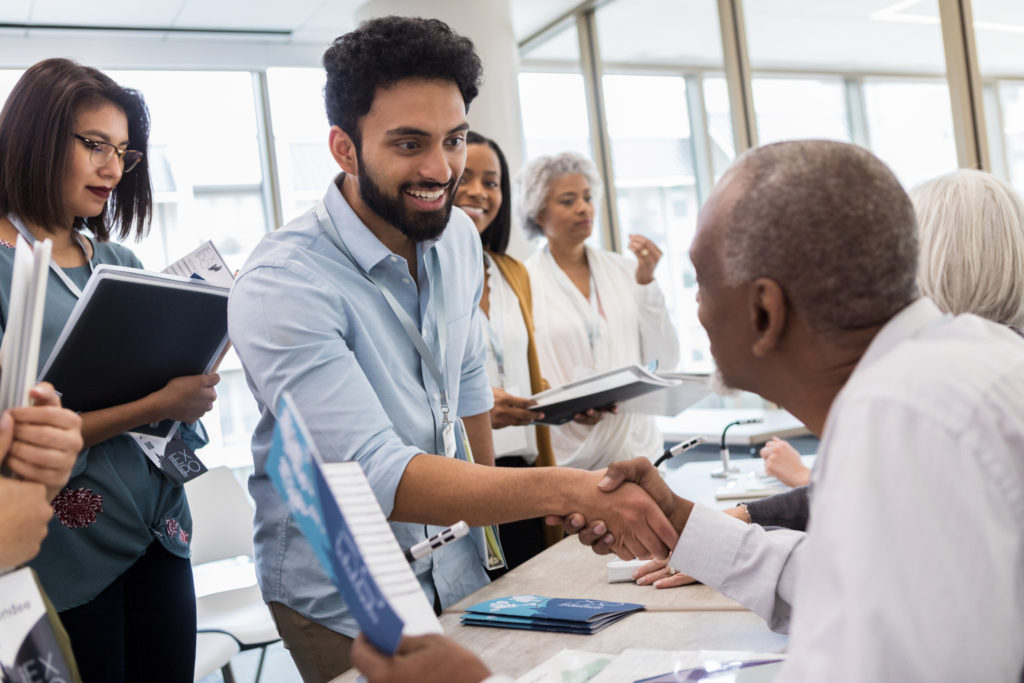 man shaking hands with other man in conference setting