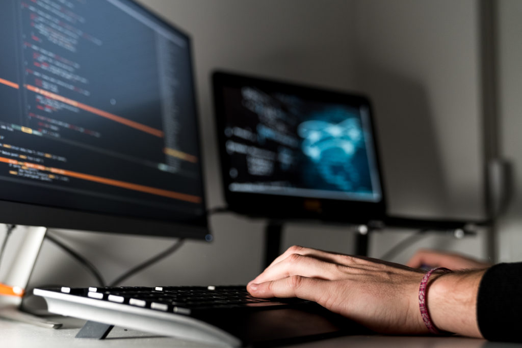 person typing on keyboard in front of two computer monitors