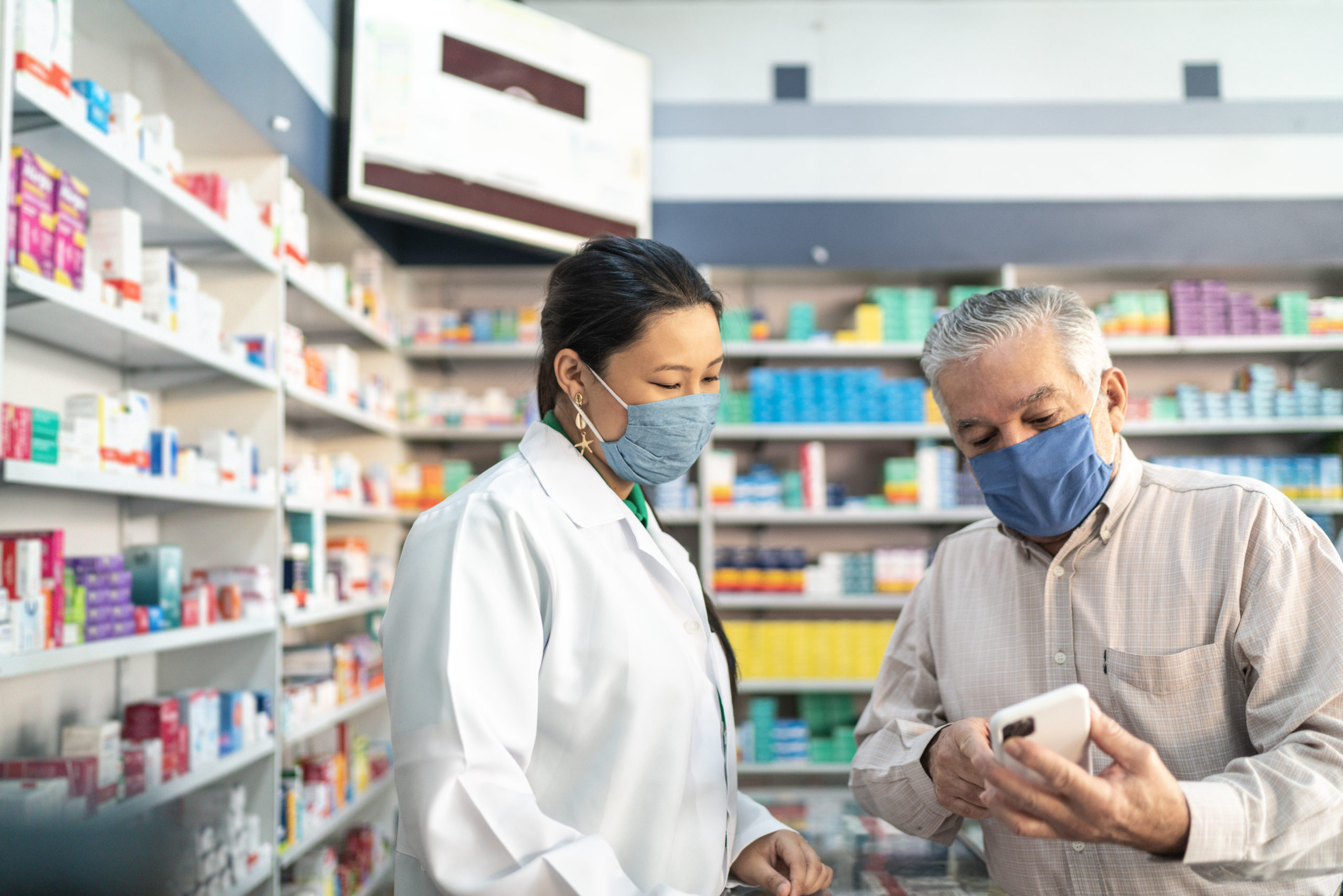 female pharmacist helping male customer