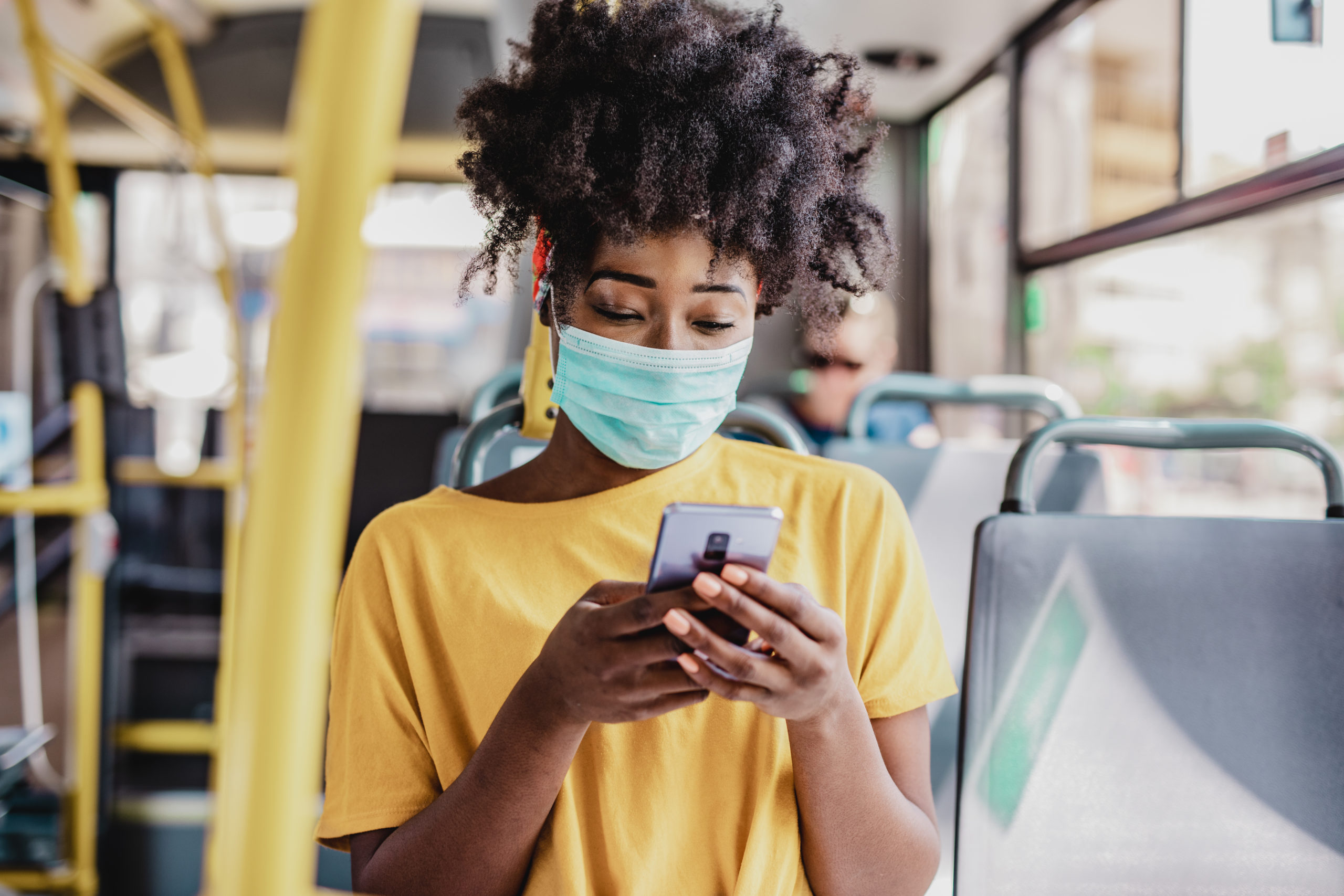 woman using phone on bus with face mask on