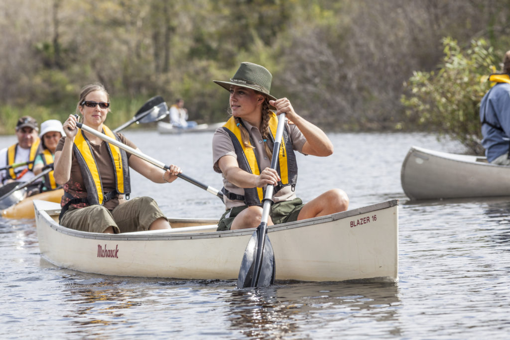 park ranger leading group of canoeing tourists
